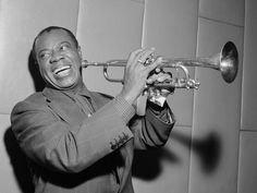 Louis laughing and playing his trumpet in 1955
