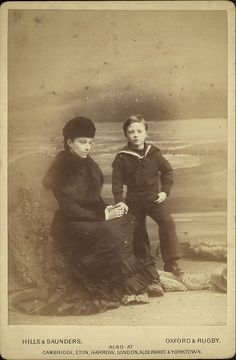 Studio portrait photograph of a mother seated on a rock on a mock beach with a dramatic seascape backdrop, accompanied by her young son in a sailor costume, by Hills & Saunders, 1880-90., via Flickr.