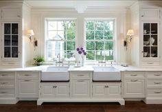 Kitchen Ideas.Dreamy kitchen with sconces flanking two apron kitchen sink. Kitchen sinks alcove with floor to ceiling white cabinets with marble countertops and traditional wood paneling as backsplash. Kitchen hardwood floors. #Kitchen #KitchenIdeas #KitchenDesign #KitchenSink #ApronSink Designed by Yunker Associates Architecture.