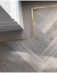 Brass inlay around chevron patterned wood flooring.