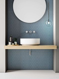 Love the tile with the circular mirror and pale wooden vanity. Clear, single globe light and cute tray of bathroom essentials. Very crisp. Love the tile with the circular mirror and pale wooden vanity. Clear, single globe light and cute tray of
