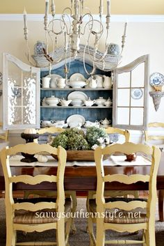 yellow/blue in dining room with white chandelier and white dishes