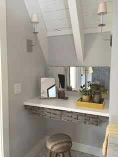 Partition walls create natural divisions for various areas in the bath, including an alcove for a vanity table, whose apron is made from two pieces of a salvaged door. Tip: Use built-ins to mask—or play up—architectural features. Here, a shelf and mirror installed between partition walls create a grooming area.
