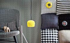 Vasemmalla Valantin Juhla-tuoli. Tuolilla  Rosendahlin puufantti, design Kay Bojesen. Valaisimena keltainen virkattu kori ja musta kangasjohto. Seinässä ylinnä vasemmalla Helga-tyyny. Sen alla Gantin tumman-sininen Velvet Edge -tyyny. Alimmaisena HKlivingin ruututyyny. Oikealla ylinnä Tensiran raitatyynynpäällinen. Sen alla Marimekon Muija-tyyny. Alinna Tikaun pellavatyynynpäällinen. Tyynyjen päällä olevat kangaskukat rekvisiittaa. |  Koti ja keittiö | Johanna Ilander | Kuvat Kirsi-Marja…