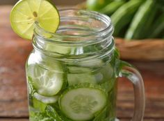 Cucumber water in mason jar with lime slice.