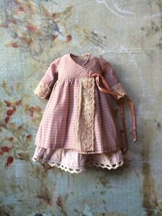 This pretty wraparound dress is made from a lovely pink striped cotton shirting, with delicate lace detailing. It fastens at the side with a ribbon and is worn over a skirt of delicate dobby cotton in pale lavender. Each set is unique and this one has lace edged sleeves.