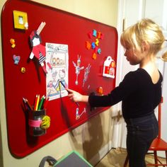 An oil drip pan spray painted red is a fun place for magnets and art!