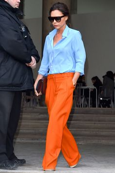 Victoria Beckham mixing orange trousers with a blue button down from her own collection.