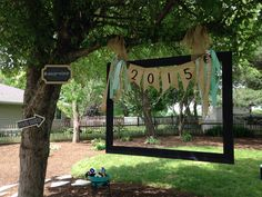 Homemade photo booth. Old picture frame hung with burlap and a few chalkboard signs added and swag.