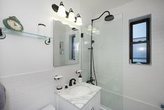 Airbnb Remodel with detachable fixtures and vanity lights. Window in an small white bathroom. Glass standing shower with a marble top sink. Small White Bathrooms, Summer In Nyc, Standing Shower, Small Vanity, New York Homes, Kitchen Upgrades, City Living, Marble Top, Vanity Lighting