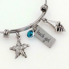 "Our classic Beach Girl bracelet continues to be a top seller!  I mean....who doesn't love the beach, right?!  features a stainless steel rectangle charm that measures 3/4"" x 3/8"" and is laser engraved with ""Beach Girl""our own custom fontAn aqua channel set Swarovski crystal accentsTibetan silver shell, and Tibetan silver starfish charm also accentsBangle bracelet is a thick gauge stainless steel and measures..."