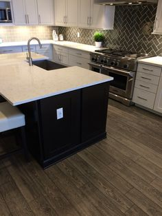 A builder design center had to find something for today's consumers that like white cabinets and grey tones. Mannington's Black Forest Oak from the Restorations collection was the answer.