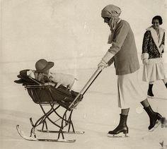 Pram on skis (sledge) on the ice, pushed by mom on skates. St. Moritz, Switzerland, 1926