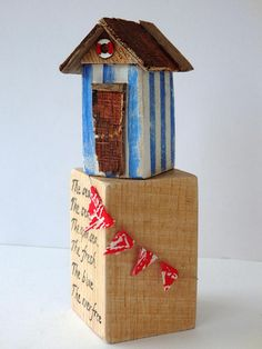 Theres a lot of beach huts near to where I live on the south coast of the UK, this one is a mix of inspiration from many I have seen. Ive used reclaimed wood and driftwood Ive collected to make this pretty little hut. Ive painted it is classic seaside colours of white and blue and its