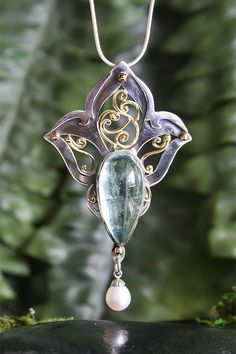 Mermaid's Treasure. Lovingly handmade in sterling silver, 18k gold, the most interesting Aquamarine cabachon filled with the most unusual inclusions, and garnished with a freshwater pearl. This pendant was a 3 day journey, building and designing until the piece spoke for itself. 2 1/2 inches in length and 1 1/2 inches in width, this delicate pendant displays grace, beauty, innocence and promises of a magical land…