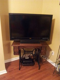 So excited!!!  I have one of these in storage...a TV will be perfect on it!!Antique sewing machine used as TV stand.