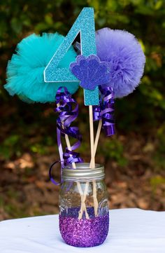 $18.50 Under the Sea Birthday Party Centerpiece Table Decoration *Please note that current processing time is up to 2 weeks plus shipping time. If you need an item sooner please message me BEFORE placing the order.*** This listing is for a custom Under the Sea centerpiece. Please note letter at checkout. You will receive: 1 Letter stick made from glittery turquoise card stock and adorned with a purple seashell 1 lavender and 1 aqua pom pom stick adored with purple metallic ribbon 1 purple gl