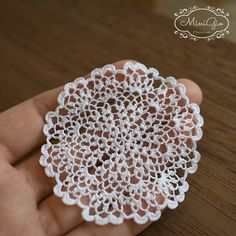 One miniature crochet doily, handmade with viscose embroidery thread and a tiny hook, in white. It has a diameter of 6.5 cm (2 1/2 in) This doily will give a romantic touch to you dollhouse, perfect for 1:12 scale, the stitches are so small that it can also be used in 1:24 scale. Each doily is washed after finished and blocked with a lot of pins in a flat surface, it will lie flat on your miniature table allowing for cups or flower arrangements to sit and look true to scale. It also c...
