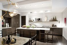 DESIGN TIP – Blend In Awkward Elements... Did you notice the range hood/exhaust in the photo below? Probably not, because the designer, Steffani Aarons, placed shelving on either side, and as a result, it just blends into the scene instead of awkwardly standing out like so many of the range hoods we see in kitchens.