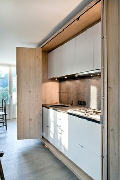 Puertas de acordeón en madera para ocultar esta cocina en la reforma de un apartamento.
