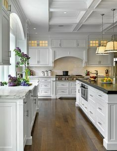 Beautiful kitchen with coffered ceiling, white kitchen island with beveled ebony stained butcher block countertop, small round sink in kitchen island, Robert Abbey Chase Pendants, white kitchen cabinets with marble countertops glossy subway tiles backsplash and farmhouse sink.