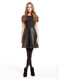Fitted top, black leather circle skirt, opaque tights, booties - accessorise with a statement necklace, wavy hair, red lips and false eyelashes!