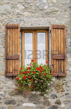 geranios: Imagen de una ventana de madera con paredes de piedra.