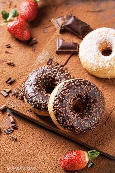 Chocolate and sugar donuts with fresh strawberries and dark chocolate served on cutting board with cocoa powder as background. Natasha Breen by 500px.com.
