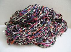 Fabric scraps into 'yarn' -- spin the yarn by wrapping the fabric strips around a core yarn, overlapping each new strip and tucking the ends in as you go along.