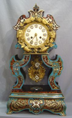 A most unusual and striking boulle clock. Decorated with ormolu mounts having boullework of inlaid brass and tortoiseshell stained in different colours. The scrolling pillars terminate in eagles' heads and are decorated with mother-of pearl flowers. The elaborate ormolu pendulum has a bird in foliage with porcelain flowers. The dial with 12 porcelain cartouches and superb gilt bronze hands. 8 day bell striking movement. Circa 1850..........Gavin Douglas Antiques