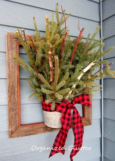 Barnwood frame all decked out for the winter season. Fill a bucket with treetop bundles, and dogwood and birch branches from the yard. The simple, buffalo plaid bow completes the country look.