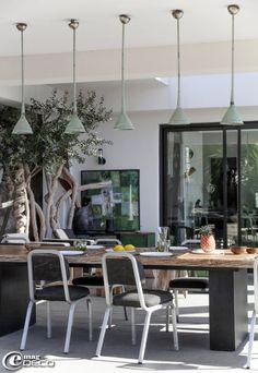 A 'La Suite Cassis', une grande table composée de plateaux de bois non avivés et d'un piètement métallique réalisé par un ferronnier de Cassis entourée de chaises des années 1960 chinées à Marseille, sous des trompes marocaines oxydées détournées en suspensions