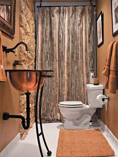 A new hammered-copper sink and canvas shower curtain transform this bath. The sink, a vessel-style bowl, sits in an iron base and is paired with an aged bronze faucet. Copper Bathroom, Bathroom Fixtures, Brown Bathroom, Southern Living Rooms, Steampunk Bathroom, Steampunk House, Basement Bathroom, Bathroom Ideas, Washroom