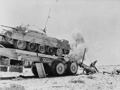 Staged photograph of 'enemy shells' exploding nearby as the crew of a Scammell Pioneer tank transporter recovers a damaged Crusader tank, 8 June Army Vehicles, Armored Vehicles, Crusader Tank, North African Campaign, Old Lorries, British Army, British Tanks, Afrika Korps, Military Pictures