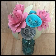 First 1st Anniversary Paper Flower Bouquet in Vase. This beautiful handmade paper flower arrangement would be a great new baby gift in the colors shown! It features 3 large pink roses with pearl centers, 6 spiral flowers and comes in a glass vase. It stands about 11 inches tall. You can customize this arrangement by choosing your flower and vase colors. If you would like other colors, please fill out the customization options with the following information: 1. Rose color (choose one…
