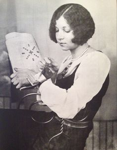 """The 1920s brought a crossword puzzle fad to the United States.  This young woman looks up """"Egyptian Sun God"""" in the world's smallest crossword puzzle dictionary, strapped to her wrist.  (From This Fabulous Century—1920-1930. Tumblr"""