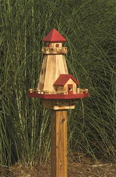 Lighthouse Bird House and Feeder from DutchCrafters Amish Furniture. A great gift for the sea and/or bird lover, this solid wood birdhouse and feeder features a unique design, is available in 4 colors, has a removable roof for easy filling, removable sides for easy cleaning, and 4x4 post bracket for mounting. #birdhouse #birdfeeder #wooden #unique #lighthouse #backyard #inthegarden