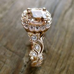 Fine vine engagement ring with morganite and diamonds. Gem specs: natural morganite, 7.8 x 7.8 mm square cushion cut. Morganite is prong-set with a halo of diamonds. Ring counts 34 diamonds of excellent quality with 0.34 ct total weight. Cast in 14K, showing vine in fine detail