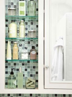 Supplement your medicine cabinet with additional shelves next to the unit. Glass shelves almost disappear against tiled wall. Pretty glass jars and decorative containers hold lotion, soap, and other toiletries.
