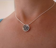 This domed pendant is made of sterling silver, using an ancient technique called granulation. The disc has been cut out of sterling silver sheet