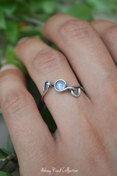Moonstone Silver Wire Wrapped Ring This unique wire wrapped ring contains a lovely Rainbow Moonstone encased in sterling silver filled wire. This dainty ring can be worn by itself or together as a stacking ring with your other favorites! The moonstone is separately attached to