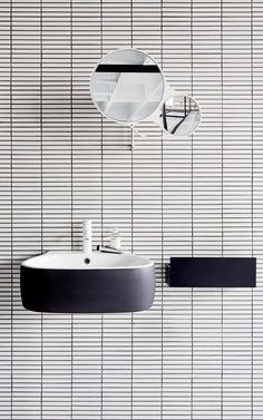 floating sink + white tile + black grout + round mirror