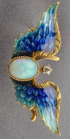 Art Nouveau 14kt Gold, Enamel, and Gem-set Pin, Riker Bros., designed as basse taille enamel wings centring a bezel-set opal, diamond highlight, wd. 1 3/8 in., maker's mark.