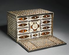 AN OTTOMAN TORTOISESHELL AND MOTHER-OF-PEARL TABLE CABINET, TURKEY, CIRCA 17TH/EARLY 18TH CENTURY the hinged drop front revealing eleven panels with nine drawers and ivory handles, the central one featuring a mother-of-pearl flowerhead design, decorated throughout with mother-of-pearl and tortoiseshell alternating revetments in a stellar pattern on top and front and diamond trellis to sides