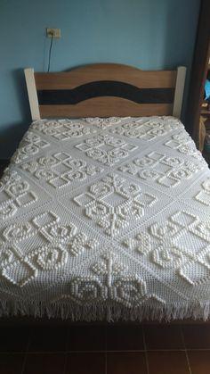 Colcha em crochê cor branca com desenhos em relevo.