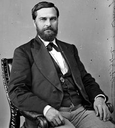 1870s - Rep. John Glover Missouri. Representative John Glover of Missouri shows the common style of pairing light colored pants with a fine frock coat and low cut vest. Note his short hair and slicked down style paired with the neatly trimmed full beard that was so popular. His small bow tie with pointed short, pointed ends was the height of fashion.