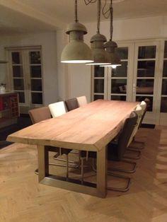 Houten keukentafel met staal en industriële lampen erboven.