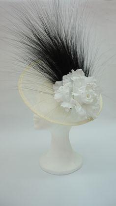 Tocado blanco y negro, base natural de sinamay con rosa blanca y barba negra.