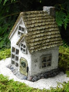 This whimsical little fairy cottage will look absolutely lovely in your miniature garden or fairy garden. The door is hinged and does swing open and closed. Painted on the door is a little green wreath. Lovely stone detail is painted at the base and a pretty shingle roof. Beautiful detail on all four sides. In the back of the house is a brick look chimney.  PLEASE NOTE THE MEASUREMENTS BELOW. ✿ Cottage measurements are approximately 5.5 Tall x 4 Wide x 4 Deep.  The cottage is made of resin…