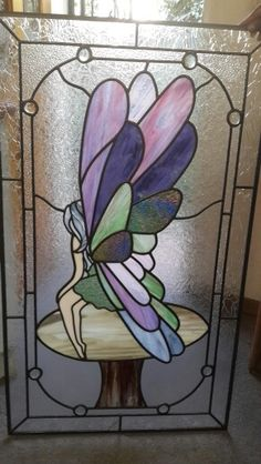 Fairy on mushroom stained glass door panel.